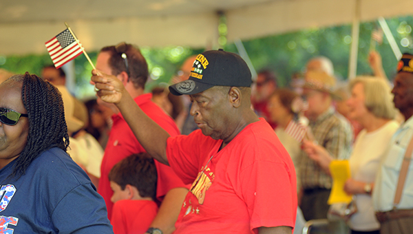 """Vietnam veteran Rich Lewis waves an American flag during the singing of """"God Bless America"""" at Monday's Memorial Day Celebration. (Advocate Staff/Andy Brown)"""