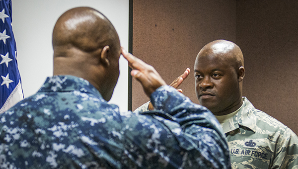 Master Sgt. Antone Scott, 96th Maintenance Group, salutes his twin brother, Lt. Cmdr. Anthony Scott, after reciting the oath of enlistment May 31 at Eglin Air Force Base, Fla. (Photo courtesy of Samuel King Jr./U.S.  Air Force)