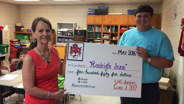 Since being diagnosed with stage four neuroblastoma, Raeleigh Jane McCartha has received an outpouring of support from the Crenshaw County community.  Pictured is Luverne High School junior class president Tyler Powell presenting a check from the junior class to Raeleigh's grandmother JoAnn McCartha, third grade teacher at LHS.