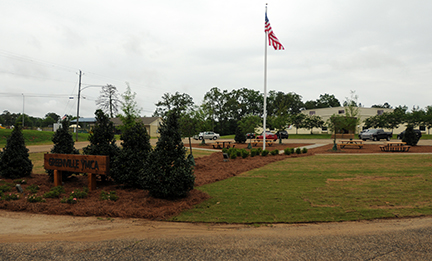 Stephenson Park, which is circular in shape, features four picnic tables, a flag pole that is lit to allow the American flag to fly day and night, sidewalks leading to the center of the park and a new wooden sign. (Advocate Staff/Andy Brown)