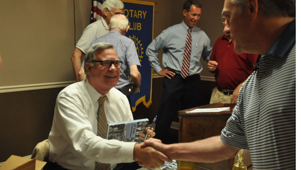 Steve Flowers is greated by Rotary Club members as he prepares to sign copies of his most recent novel. (Photo by Beth Hyatt)