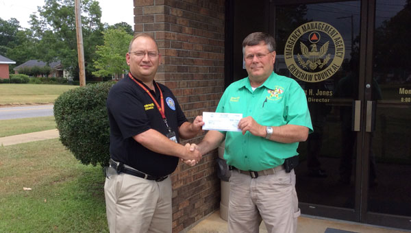 Pictured is Elliott Jones, Crenshaw County Emergency Management Agency (EMA) director, (left) presenting the check to Crenshaw County Sheriff Mickey Powell (right).