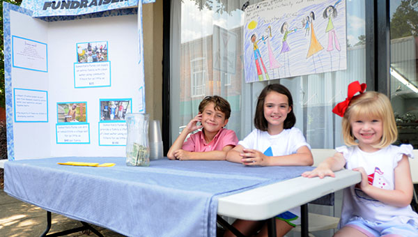 From left to right, Sam Judah McLendon, Winn Lowery and Ann Knox McLendon opened a lemondae and water stand in front of Camellia City Bakery & Deli Thursday to raise money to help provide clean drinking water for those in need around the world. (Advocate Staff/Andy Brown)