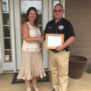 County Commissioner Michelle Stephens presents Crenshaw County EMA Director with his certificate.